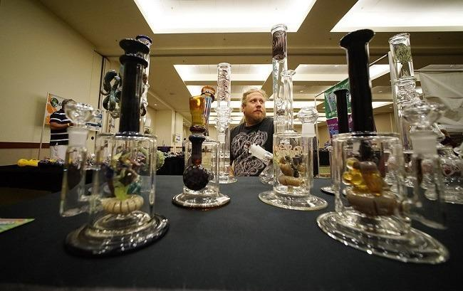 Glass artist Mark Nowicki displays his handmade bongs at the O.G Tubes booth at the marijuana expo at the Hawaii Convention Center on July 19. Image: Cory Lum, Civil Beat.