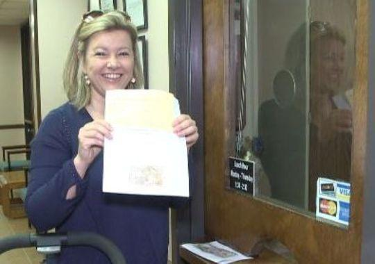 Erin Cleveland holding up Lainey's medical marijuana registration card?(Photo: Hopper, Christopher)