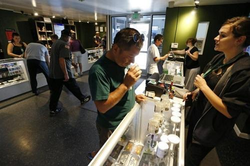 Customers shop at the Grass Station dispensary in Denver. Because of federal banking regulations, Colorado's $700-million-a-year industry runs almost entirely on cash. Image: Brennan Linsley, Associated Press via Los Angeles Times