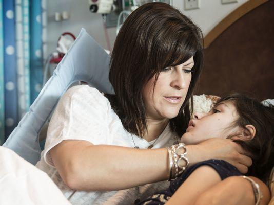 Heather Shuker comforts her daughter Hannah, 12, after a series of seizures. Photo: Lex Talamo, News21