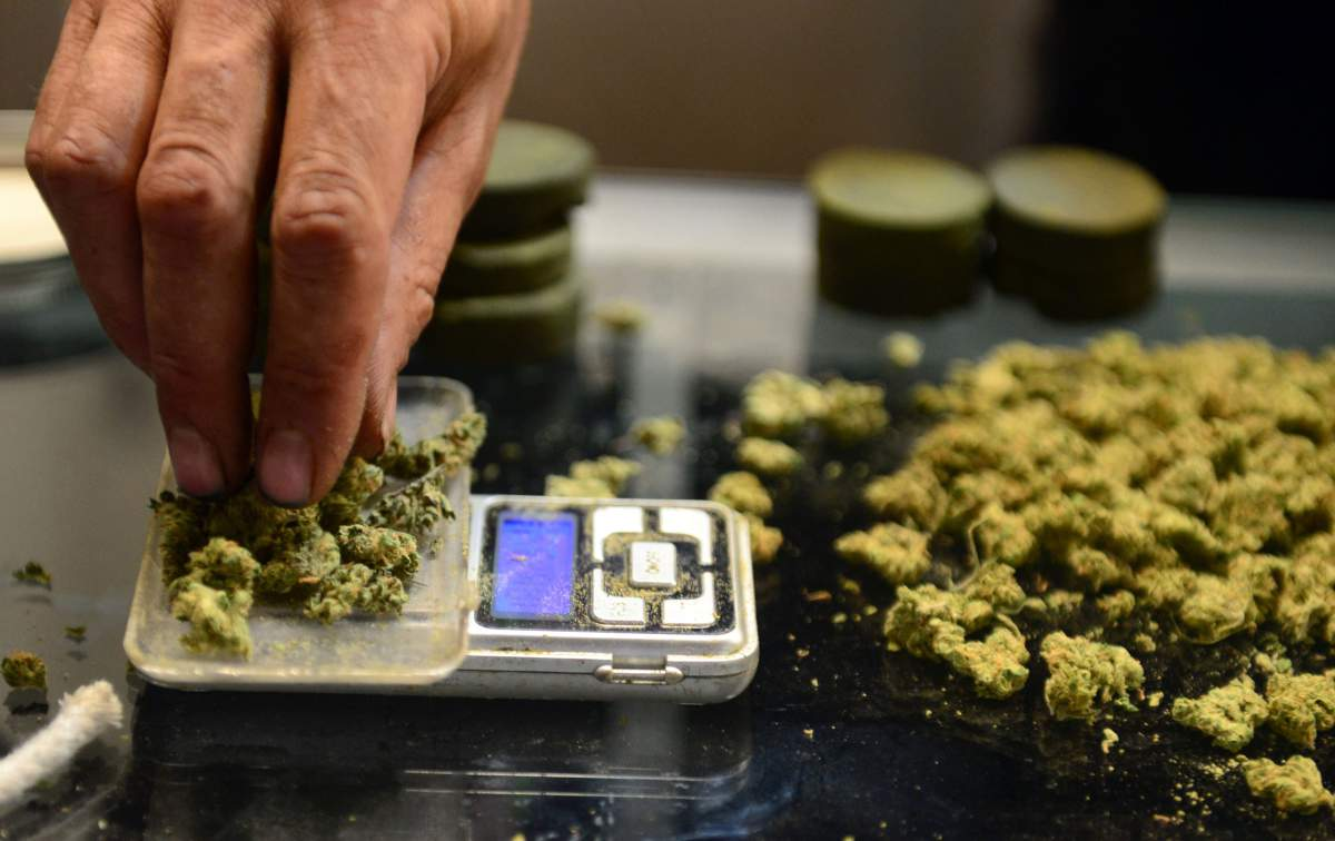 A vendor weighs marijuana for card-carrying medical marijuana patients attending Los Angeles' first-ever cannabis farmer's market in Los Angeles, July 4, 2014.