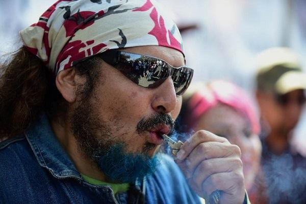 A man smokes marijuana during a rally in front of the Supreme Court of Justice in Mexico City on November 4, 2015. AFP Photo: Alfredo Estrella