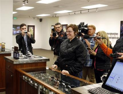 Davia Fleming, 29, center, is surrounded by media members as she becomes the first shopper at Shango Premium Cannabis, in Portland, Ore. On Oct. 1, 2015. Oregon marijuana stores have begun sales to recreational users. (AP Photo/Timothy J. Gonzalez)