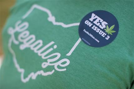 Michael McGovern, a representative from ResponsibleOhio, a pro-marijuana legalization group, wears a sticker during a promotional tour stop at Miami University, Friday, Oct. 23, 2015, in Oxford, Ohio. AP Photo/John Minchillo