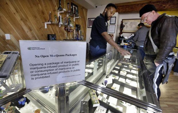 Cannabis City clerk Will Bibbs, left, helps a customer looking over a display case of marijuana products at the shop in Seattle. (AP Photo/Elaine Thompson, File)