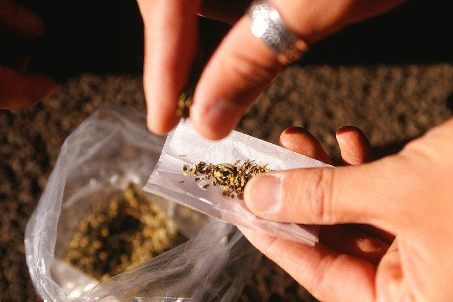 Image of cannabis being rolled into a joint
